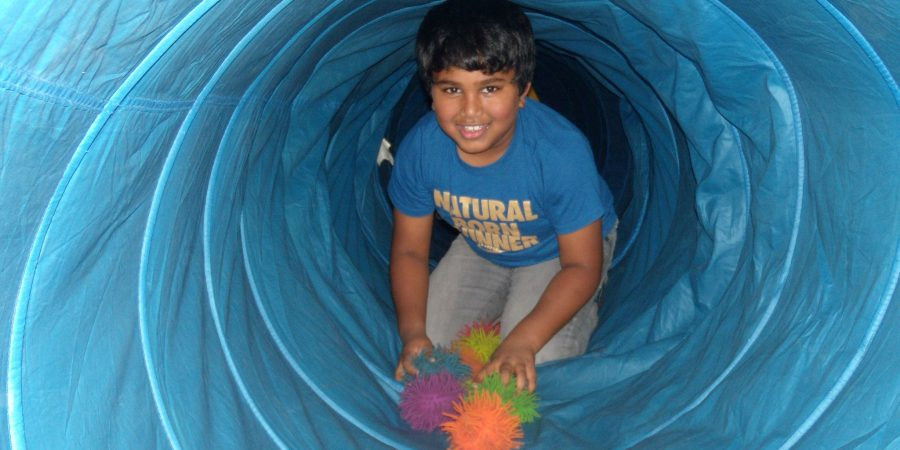 Student inside a play tube smiling.