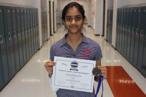 Tanisha Muralimanohar holding award