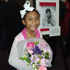 Student holds flowers and smiles beside phtoo and essay. Wearing a big white bow on top of head.