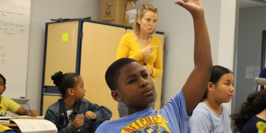 Student raising his hand in class