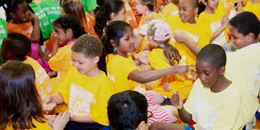 Students play rock, paper, scissors in colorful shirts.